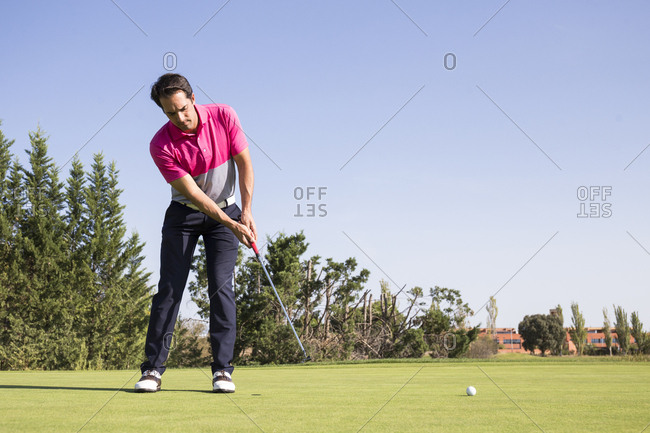 Golfer putting on green