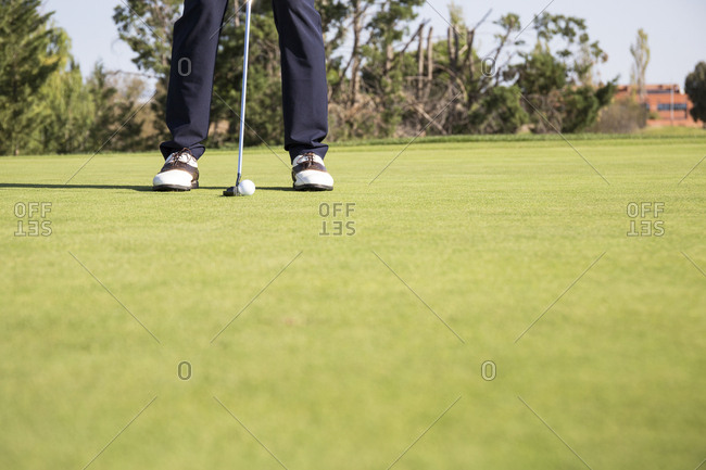 Ground level view of golfer preparing to putt the ball