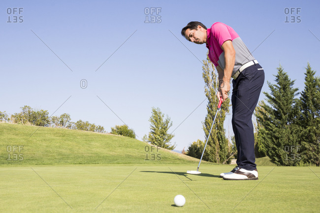 Low angle view of golfer putting the ball towards camera