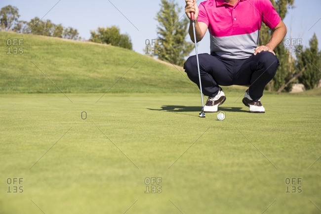 Ground level view of golfer crouching to line up putt