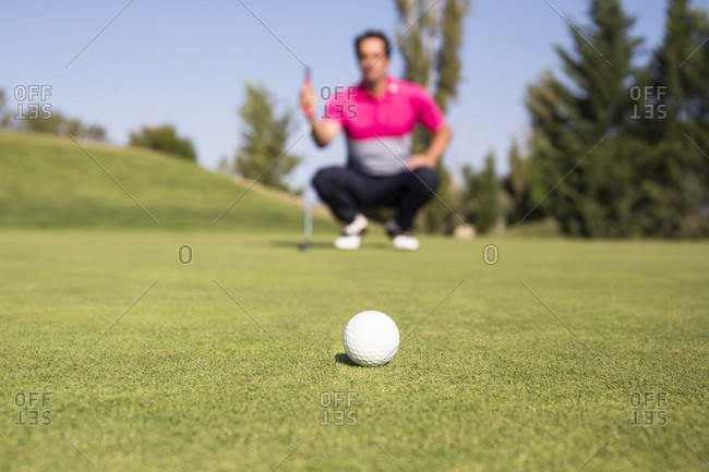 Low angle view of golfer crouching on green with ball in the foreground
