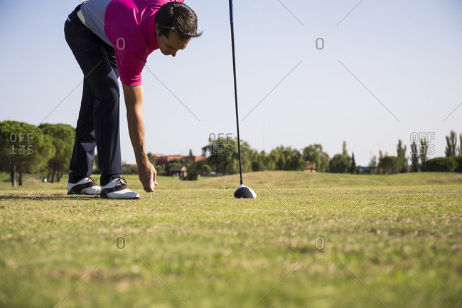 Golfer bending over to place ball on tee
