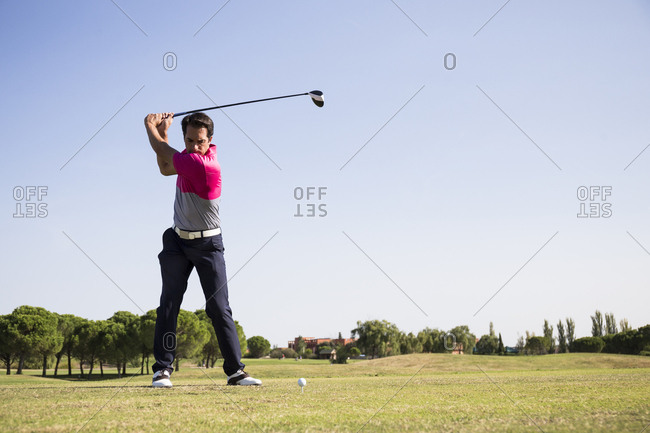 Golfer teeing off with driver