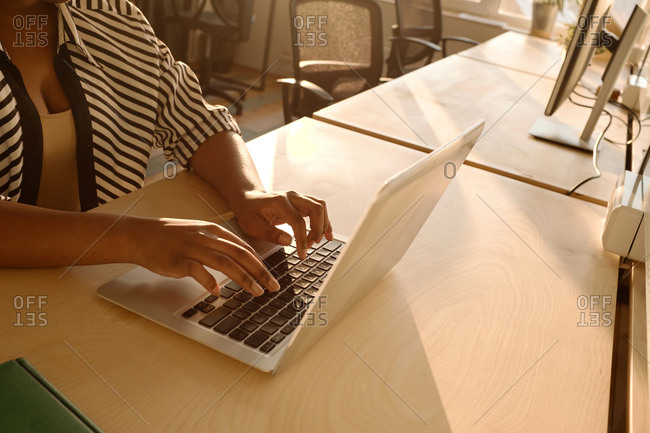 Unrecognizable African American woman typing on laptop while sitting at office table illuminated with soft evening light