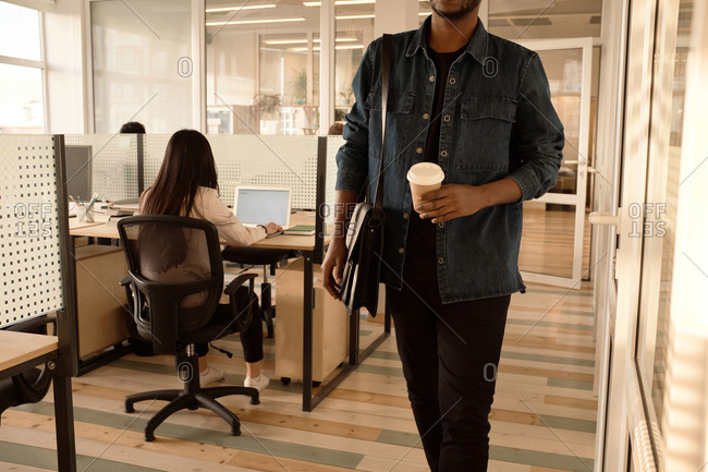 End of working day. Unrecognizable black man leaving office with coffee to go, unrecognizable woman working on laptop behind