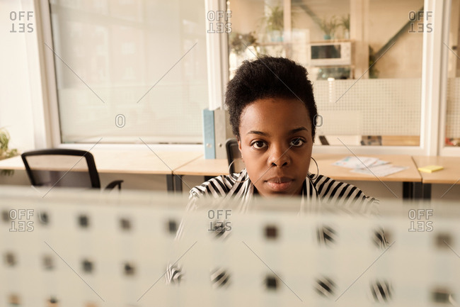 Portrait of attractive African American woman sitting at table in modern office with divider walls and looking at camera