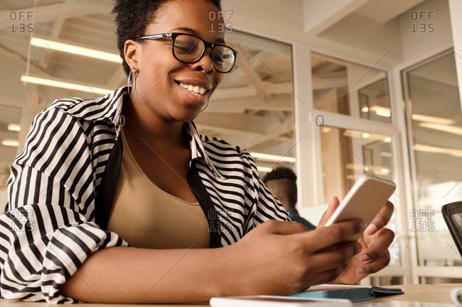 Low angle view of attractive black woman using smartphone and smiling happily while sitting at table in modern office