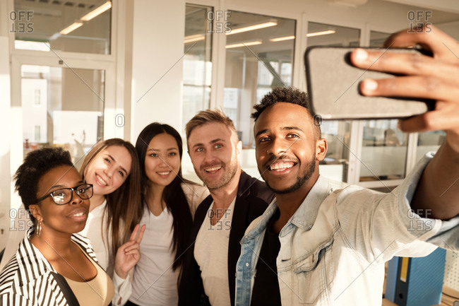 Multiethnic group of young colleagues smiling happily at smartphone camera while taking selfie in modern office