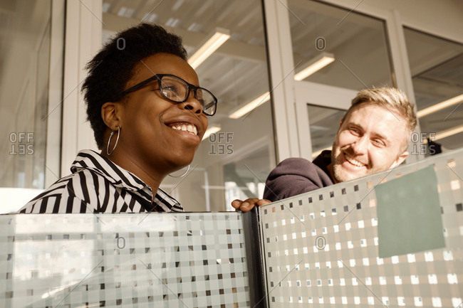 Attractive African American woman talking to her male colleague and smiling cheerfully in modern office with dividers, low angle view
