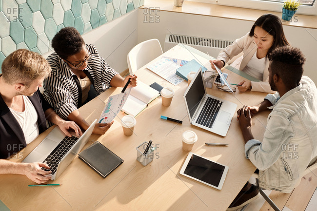 Multiethnic group of young managers sitting around table in conference room and discussing new company strategies, high angle view