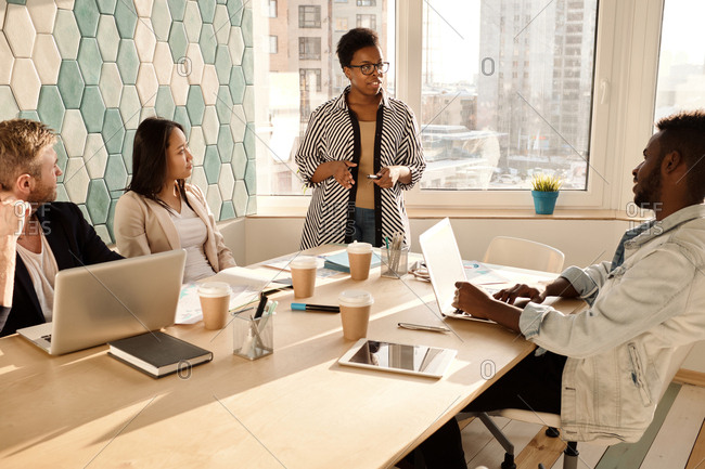 Multiethnic group of young businesspeople having meeting in conference room, stylish African American woman giving a speech
