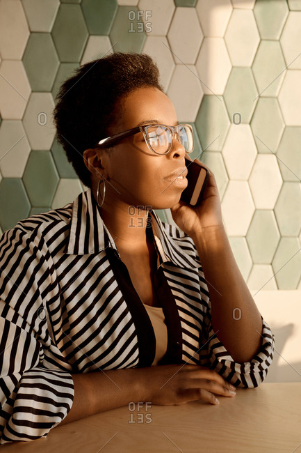 Stylish African American businesswoman in glasses talking on smartphone while sitting in modern office illuminated with bright sunlight