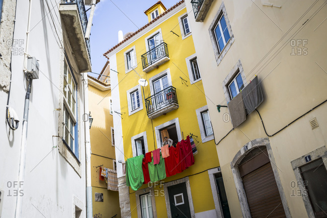 Lisbon, Portugal - March 29, 2016: A woman hangs laundry on her balcony in the Mouraria area