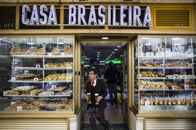 Lisbon, Portugal - March 28, 2016: A waiter brings beer to customers at a bakery