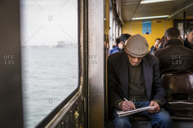 Lisbon, Portugal - March 28, 2016: An elderly man does the crossword on a ferry