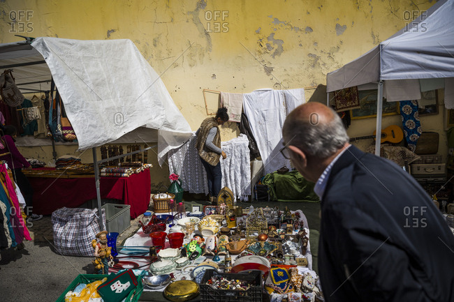 Lisbon, Portugal - March 29, 2016: A woman arranging her goods at the Thieves Market