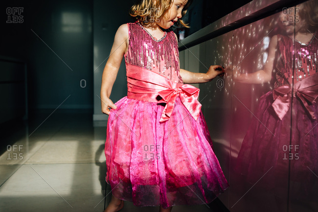 Little girl in sparkly pink dress looking at her reflection