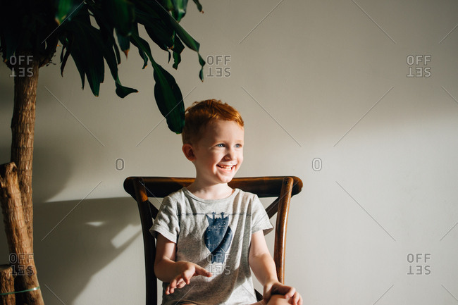 Happy redhead boy sitting in wooden chair