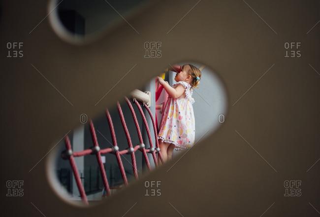 Toddler girl climbing on a jungle gym