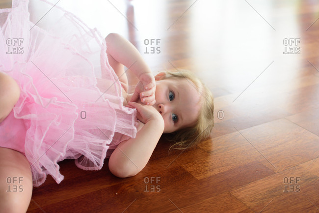Toddler girl dressed in pink ballerina outfit lying on floor
