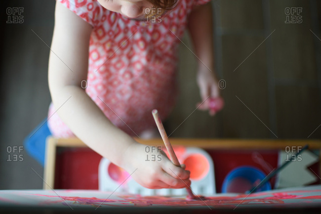 Overhead view of little girl painting on an easel