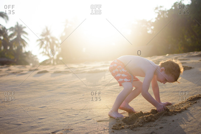 Boy digging in sand at a beach in Malaysia