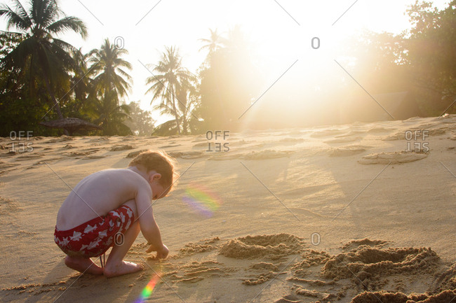 Boy digging in the sand at a beach in Malaysia