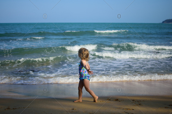 Toddler girl walking on a beach in Malaysia