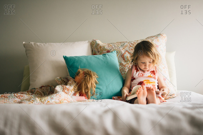 Little girl sitting in bed with book