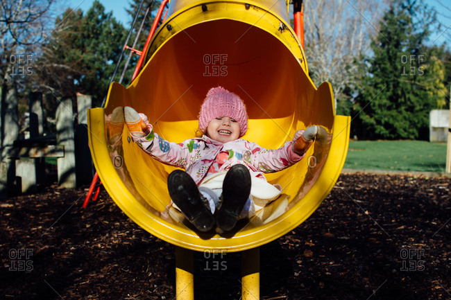 Toddler girl sliding down yellow slide