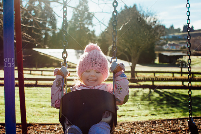 Toddler girl swinging at a park