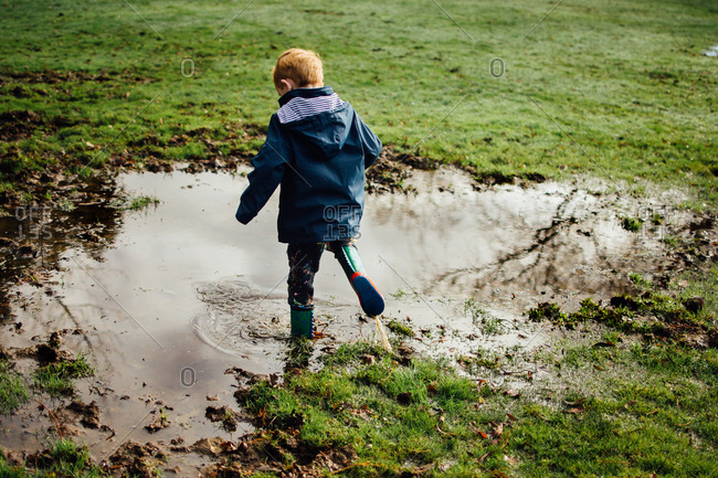 Boy playing in mud puddle