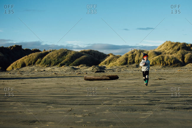 Boy running on beach in the fall