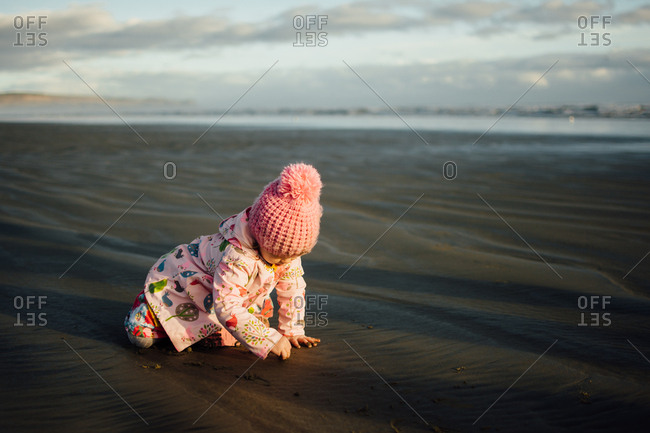 Toddler girl playing in the sand on a beach in the fall