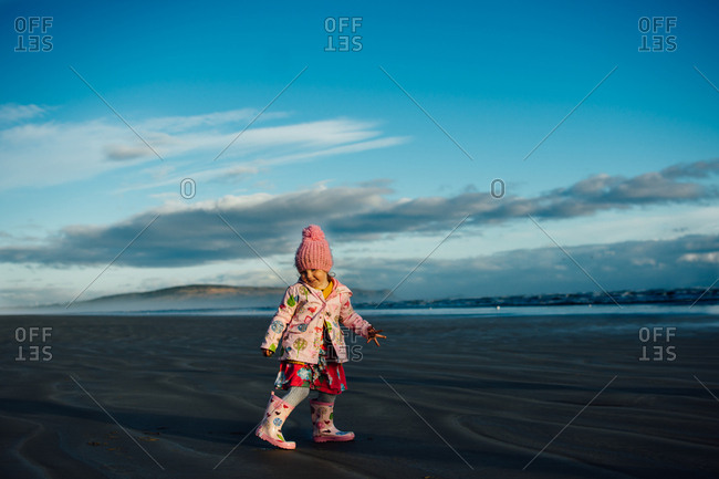 Toddler girl on a beach in the fall