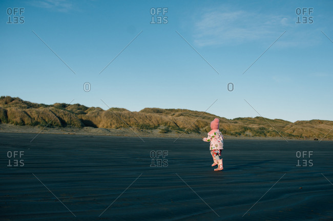 Toddler girl running on a beach in the fall