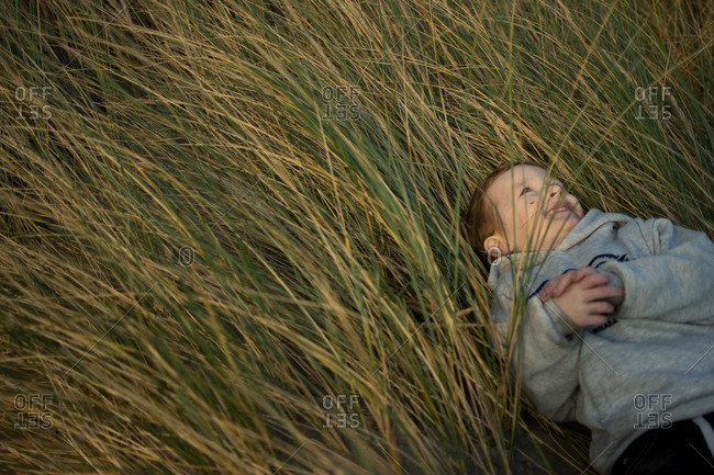 Boy lying in tall grass looking up at the sky
