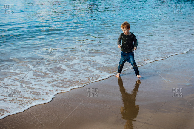 Boy walking fully clothed in waves at a beach