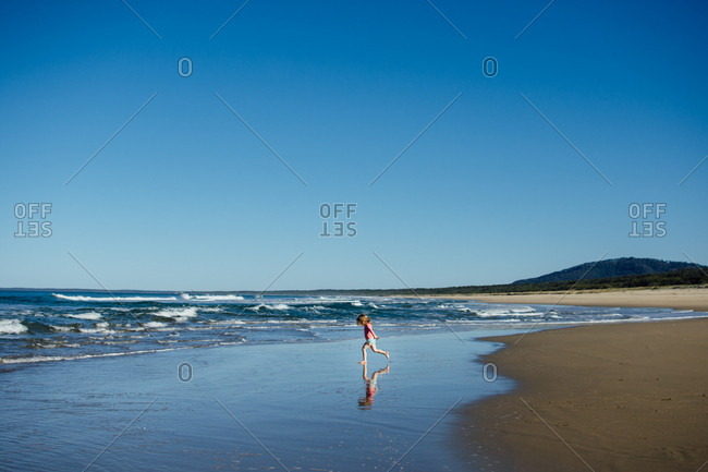 Girl running in the tide on a beach