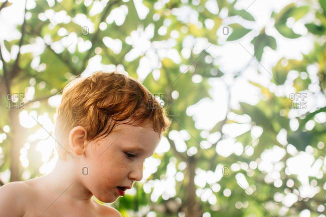 Redhead boy outdoors looking away