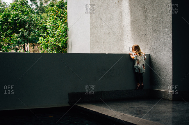 Little girl looking over ledge of a building