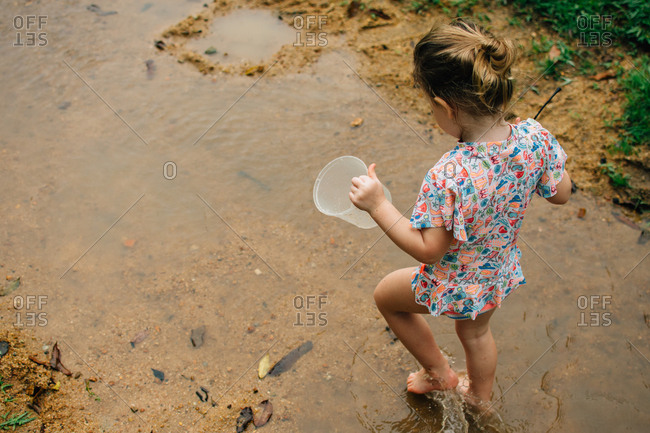 Girl playing barefoot in a puddle