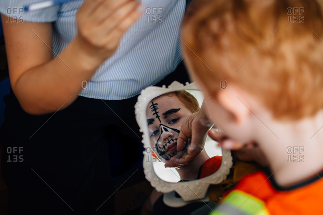 Boy having face painted for Halloween costume