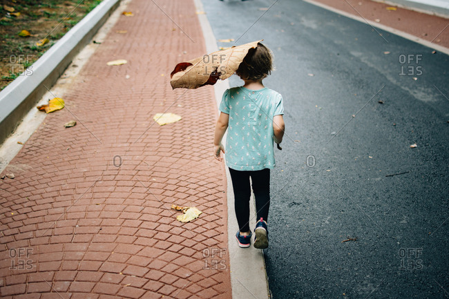Rear view of girl walking with huge leave on her head