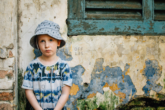 Little boy standing beside old building with peeling paint