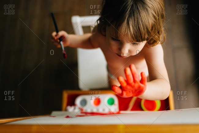 Overhead view of little girl finger-painting on an easel