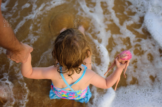 Toddler girl sitting in tide at a beach in Malaysia