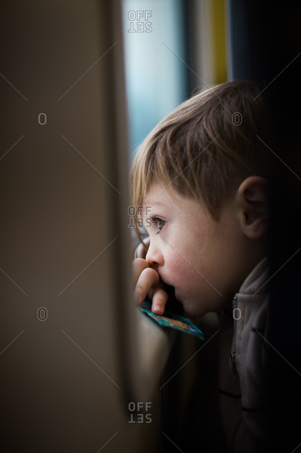 Little boy looking out the window of a train