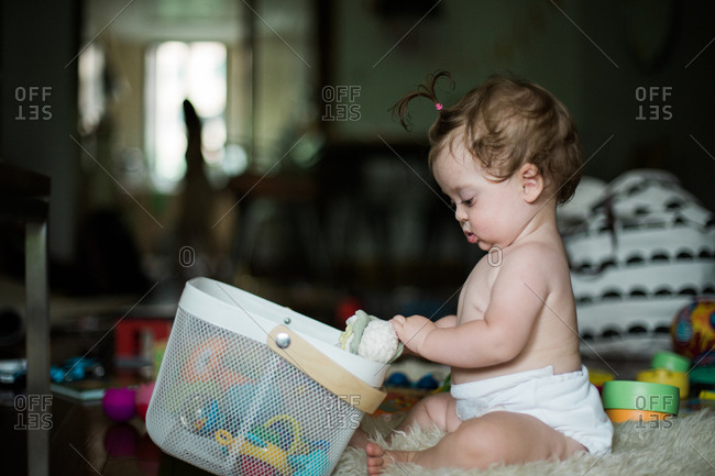 Baby in cloth diaper playing with toys
