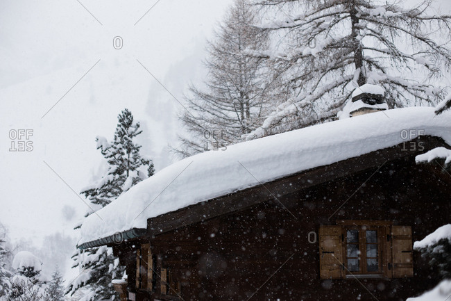 Snow against a scene of trees and a traditional mountain building